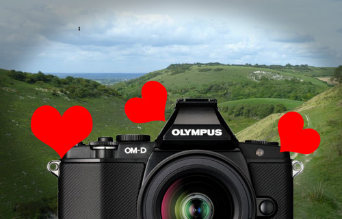 Olympus OM-D E-M5 camera and landscape background with hearts
